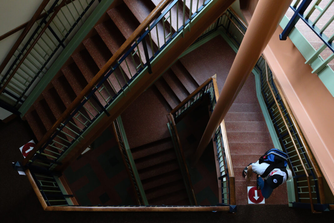 A student walks up the central staircase in Hollenbeck Hall on Aug. 16, 2020. The staircase has been designated as the only upward staircase in the building due to the COVID-19 pandemic in order to reduce contact between students. (Trent Sprague/The Wittenberg Torch)